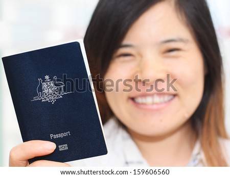 Smiling Asian Woman Holding an Australian Passport in narrow focus