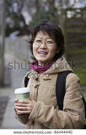 Smiling asian woman holds a coffee cup