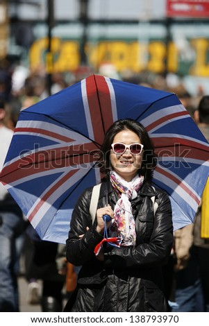 Smiling asian woman, in the middle of a crowd of Camden Street, with Union Jack umbrella - stock photo