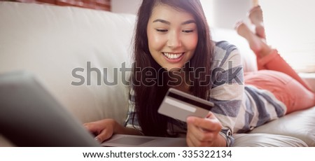 Smiling asian woman on couch using tablet to shop online at home in the living room - stock photo