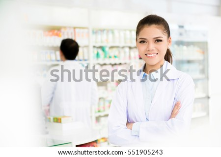 Smiling asian woman pharmacist in pharmacy (chemist shop or drugstore)