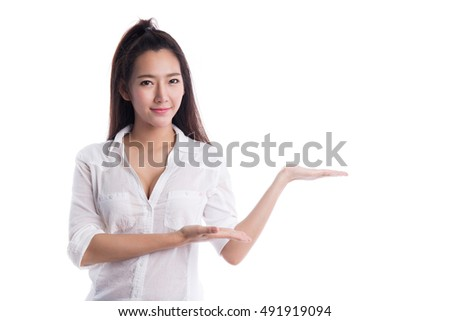 Smiling asian woman pointing or showing to copy space, isolated on white background