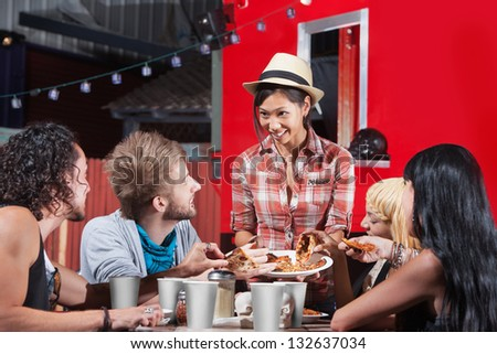 Smiling Asian woman sharing pizza slices with friends at food truck