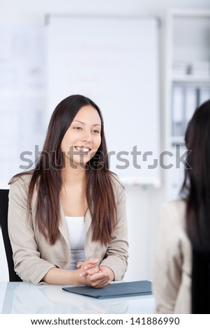 smiling asian woman sitting at desk in a business meeting - stock photo