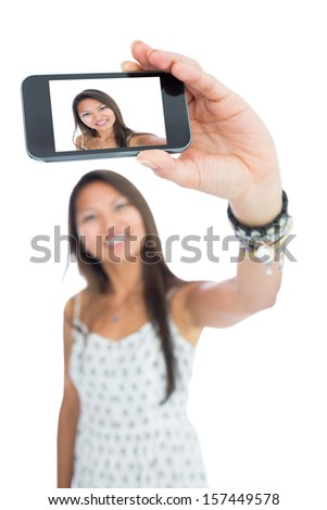 Smiling asian woman taking a selfie using her smartphone - stock photo