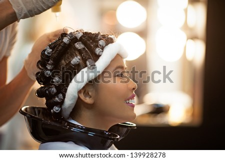 Smiling Asian woman with curlers in her hair.