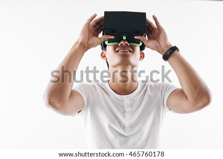 Smiling Asian young man enjoying virtual reality