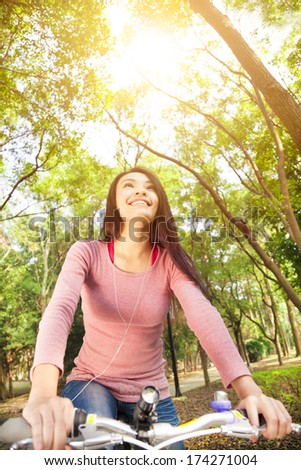 smiling  asian young woman riding bike in the forest - stock photo