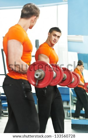 Smiling athlete bodybuilder man at biceps brachii muscles exercises with training dumbbells in fitness gym