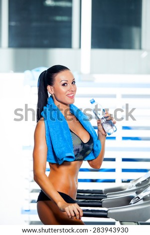 Smiling athletic woman drinking water on a treadmill - stock photo