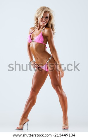 Smiling athletic woman in pink bikini showing muscles on gray background - stock photo