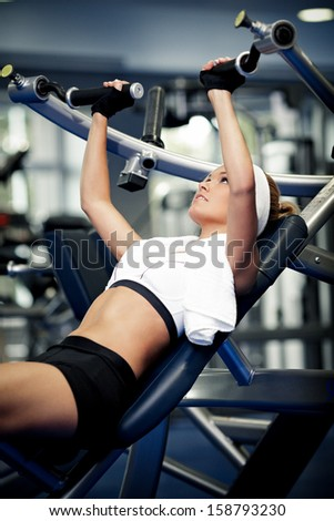 Smiling athletic woman pumping up muscles in a gym - stock photo