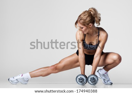 Smiling athletic woman pumping up muscles with dumbbells and stretching legs - stock photo