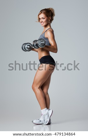 Smiling athletic woman pumping up muscles with dumbbells on gray background