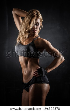 Smiling athletic woman showing muscles on dark background - stock photo