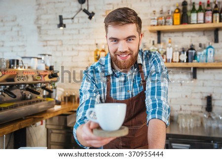 Smiling attractive bearded barista serving you cup of coffee on wooden coaster in cafe - stock photo