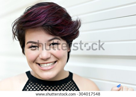 Smiling attractive brunette woman under soft natural lighting. Shallow depth of field. - stock photo