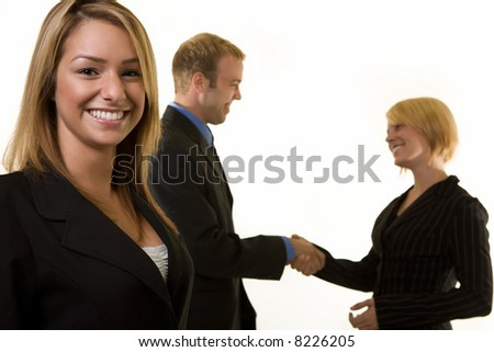 Smiling attractive business woman in focus with two business people shaking hands in the background