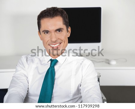 Smiling attractive businessman sitting at his desk in the office - stock photo