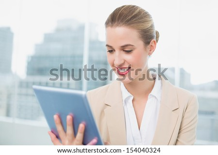 Smiling attractive businesswoman in bright office using her tablet