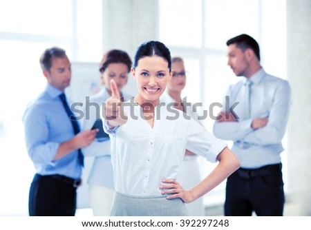 smiling attractive businesswoman in office showing thumbs up - stock photo