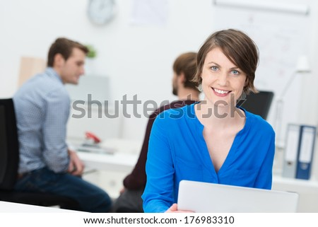 Smiling attractive businesswoman in the office sitting behind a laptop computer as her colleagues work behind her - stock photo