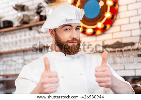Smiling attractive chef cook showing thumbs up on the kitchen - stock photo