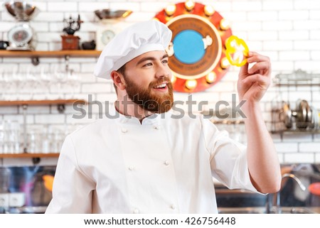 Smiling attractive cook cheif holding slice of yellow bell pepper  on the kitchen - stock photo