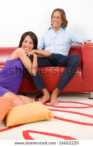 Smiling attractive couple sitting in home.