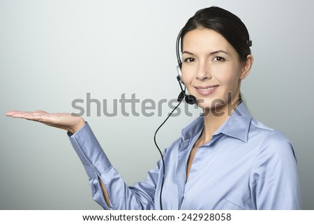 Smiling attractive, friendly woman doing telemarketing or a promotion wearing a headset and extending her empty palm for your product placement over blank grey copy space - stock photo