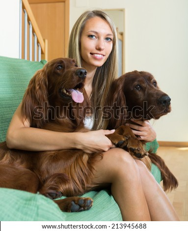 Smiling attractive girl hugging two Irish setters on sofa. Focus on girl