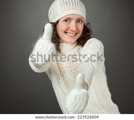 Smiling attractive girl showing thumbs up in mittens, gray background