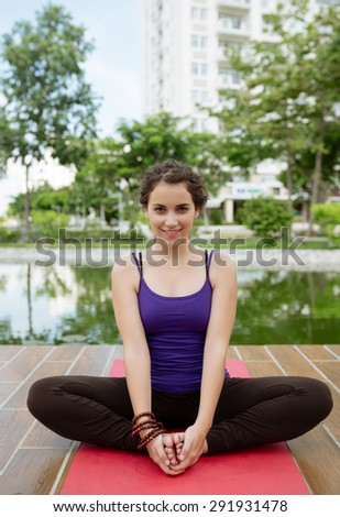Smiling attractive girl sitting in yoga position on the mat - stock photo