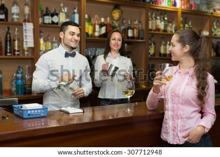 Smiling attractive girl standing at bar with glass of wine and flirting with barman. Focus on guy