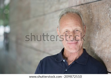 Smiling attractive grey-haired man standing alongside a receding exterior wall looking at the camera with copyspace - stock photo