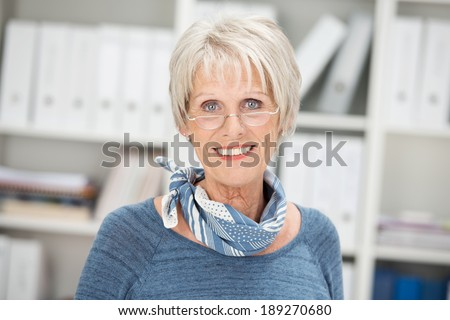 Smiling attractive grey-haired senior businesswoman wearing glasses standing in her office looking at the camera - stock photo