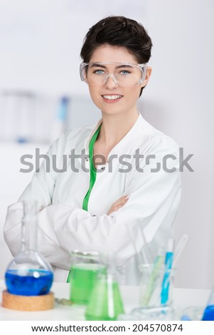 Smiling attractive laboratory technician wearing safety goggles standing with folded arms at her bench full of glassware with chemical solutions - stock photo