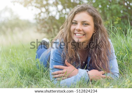 Smiling attractive long hair teenage girl lying in the grass and looking at the camera.
