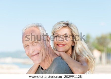 Smiling attractive middle-aged couple relaxing at the beach posing together for a portrait in the hot summer sun - stock photo