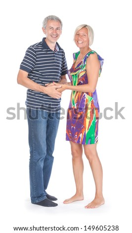 Smiling attractive middle-aged couple standing close together looking at the camera isolated on white