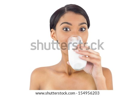 Smiling attractive model drinking milk posing on white background