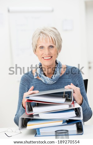Smiling attractive senior businesswoman sitting at her desk holding onto a tall stack of office files - stock photo