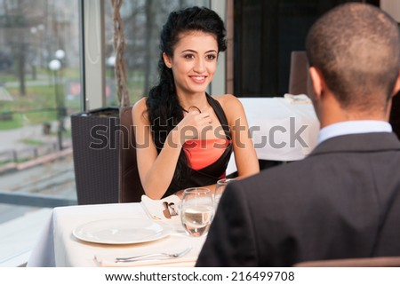 Smiling attractive woman and man having discussion. back view of man listening to girl at lunch break - stock photo