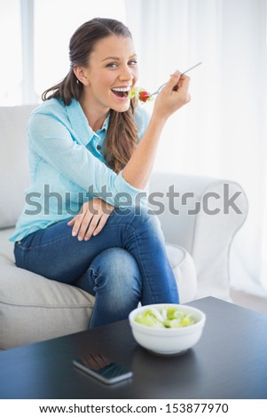 Smiling attractive woman eating healthy salad sitting on cosy sofa - stock photo