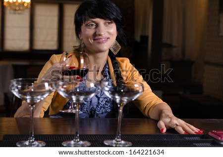 Smiling attractive woman enjoying a drink of red wine while sitting at the counter in a hotel bar or nightclub socialising with friends - stock photo