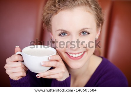smiling attractive woman enjoying cup of coffee in a coffee shop - stock photo