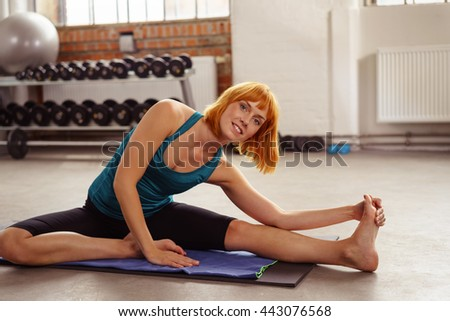 Smiling attractive woman exercising in a gym working out on a yoga mat on the floor doing stretching exercises - stock photo