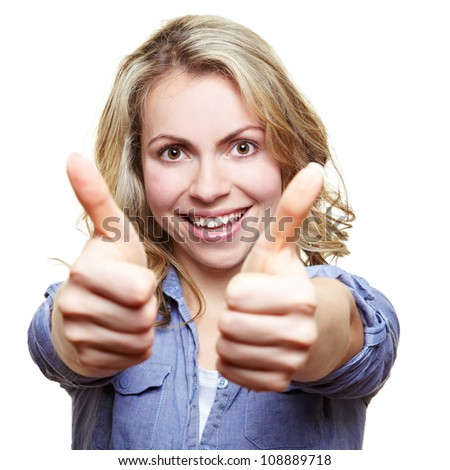 Smiling attractive woman holding her two thumbs up - stock photo