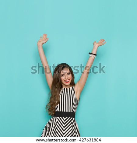 Smiling attractive woman in black and white striped dress standing with arms raised and looking at camera, Three quarter length studio shot on turquoise background. - stock photo