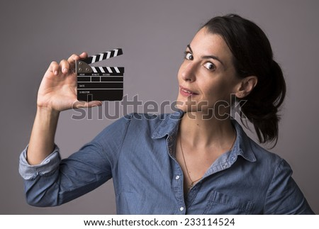 Smiling attractive woman in jeans shirt holding a movie clapper with gray studio background - stock photo